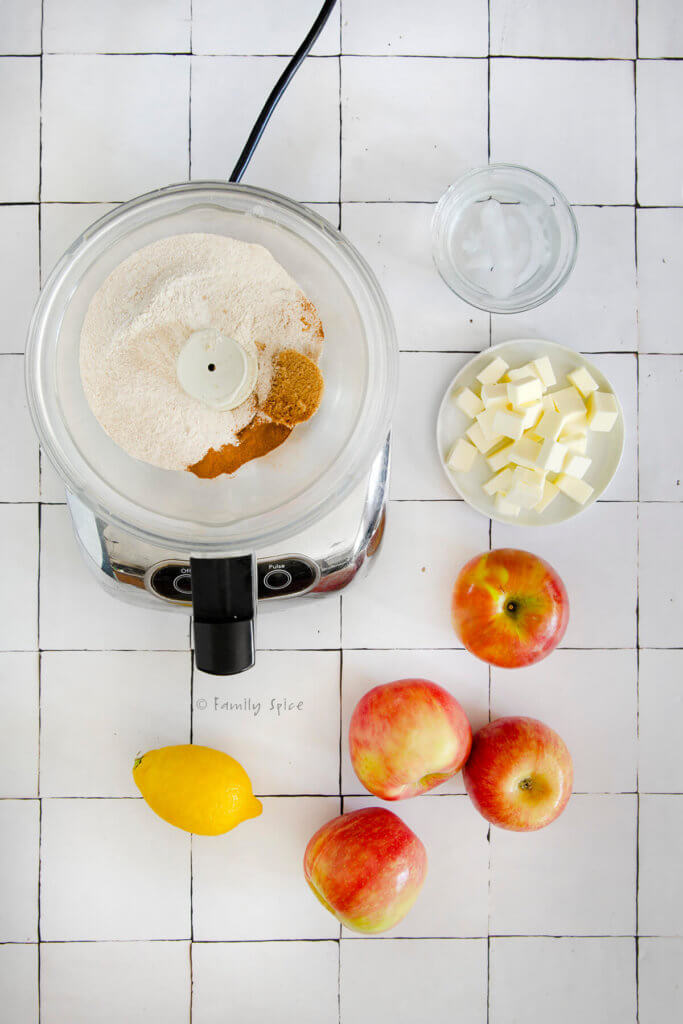 Food processor with flour, sugar and cinnamon with cubes of butter, water, apples and lemon