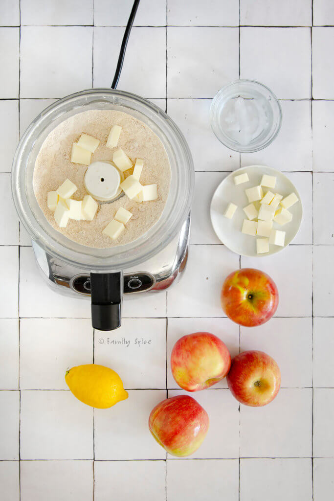 food processor with flour mixture and cubes of butter next to apples, lemon, more butter and ice water