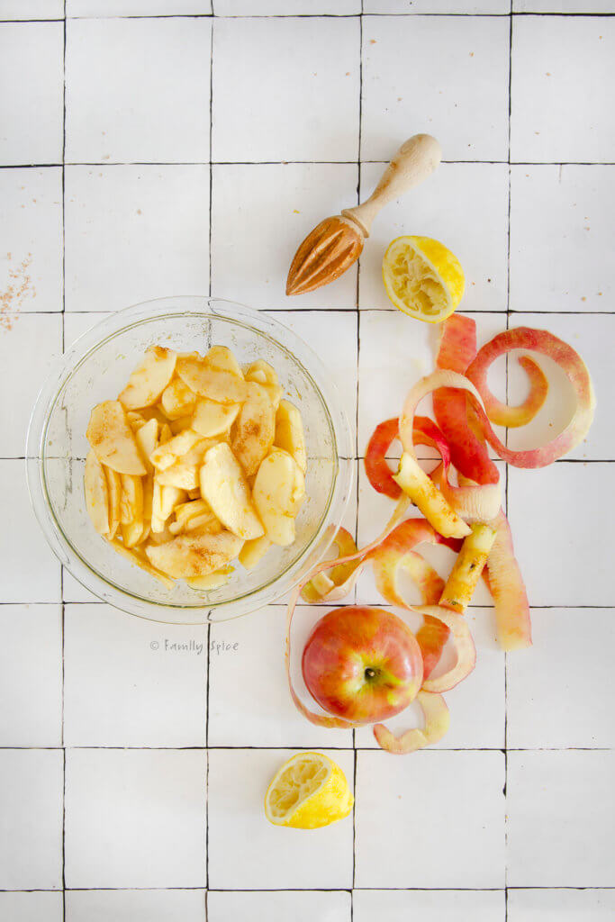 A bowl of sliced apples mixed with brown sugar and cinnamon surrounded by apple peels and juiced lemons