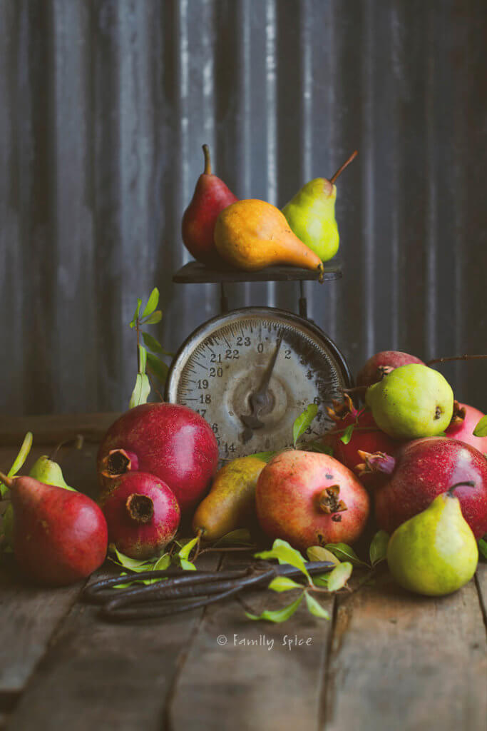 Red, brown and green pears with pomegranates on a rustic kitchen scale with scissors