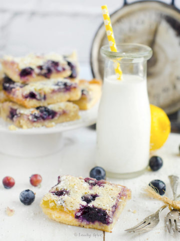Closeup of a blueberry lemon bars with a glass bottle of milk