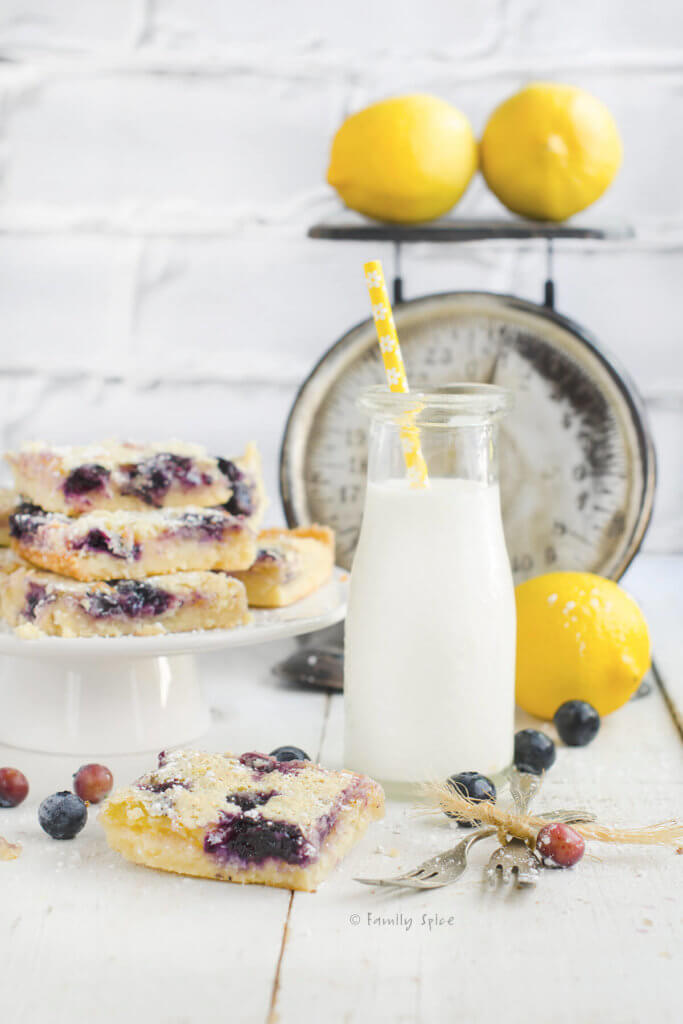 Blueberry lemon bars with a glass bottle of milk and an antique scale in background