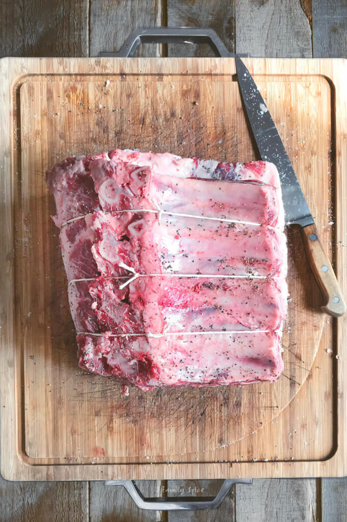An uncooked standing rib roast tied with kitchen twine on a cutting board with a sharp knife next to it