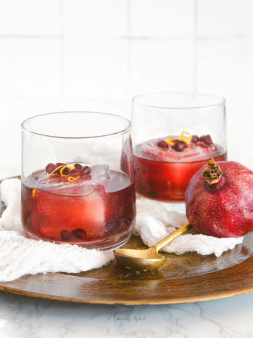 Sideview of two glasses with a large ice cube and pomegranate gin sling inside garnished with pomegranate and orange zest on a golden tray
