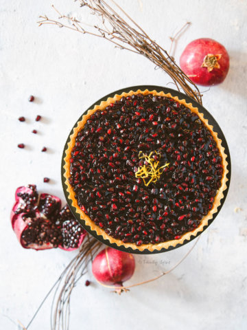 Overhead view of a pomegranate fruit tart garnished with lemon zest with pomegranates around it