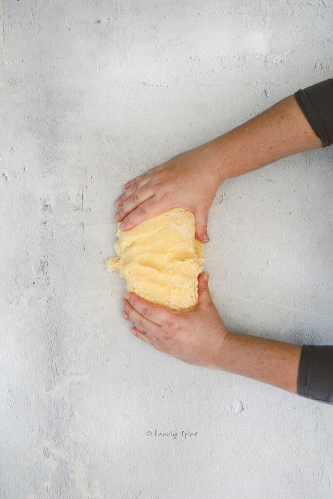 Overhead view of two hands working pie dough