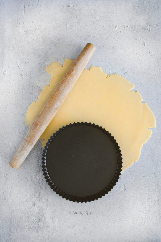 Rolled out pie dough with a wooden rolling pin and empty tart pan next to it
