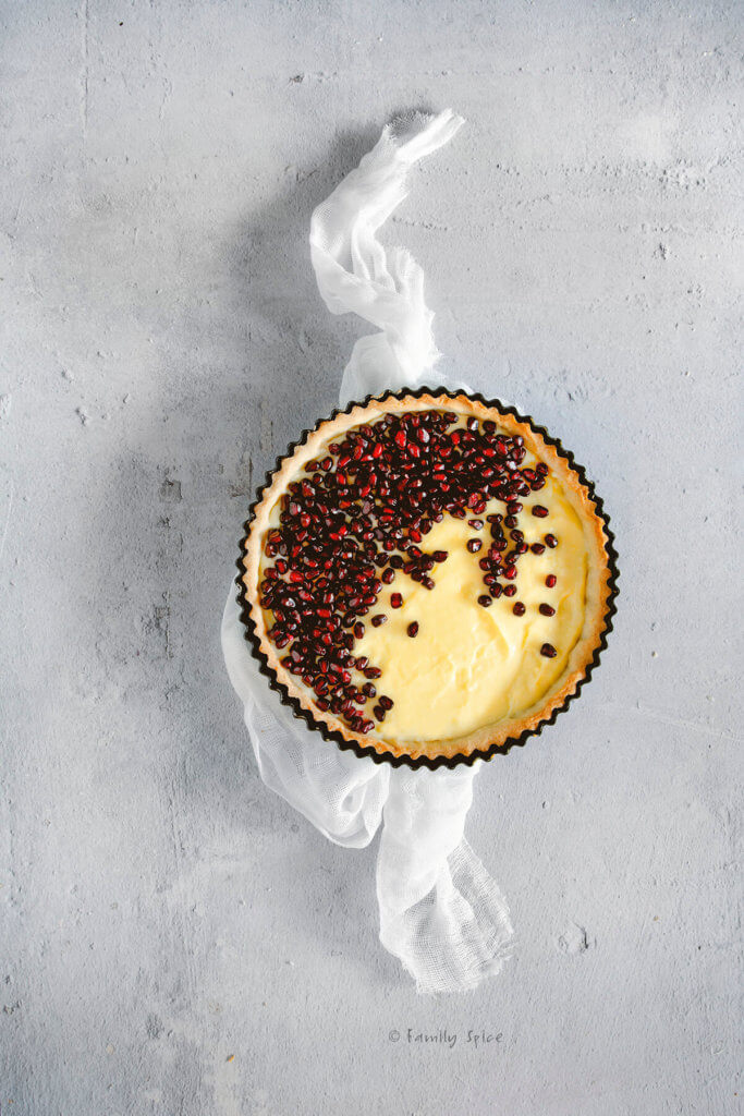 Spreading pomegranate arils over a tart shell filled with pastry cream