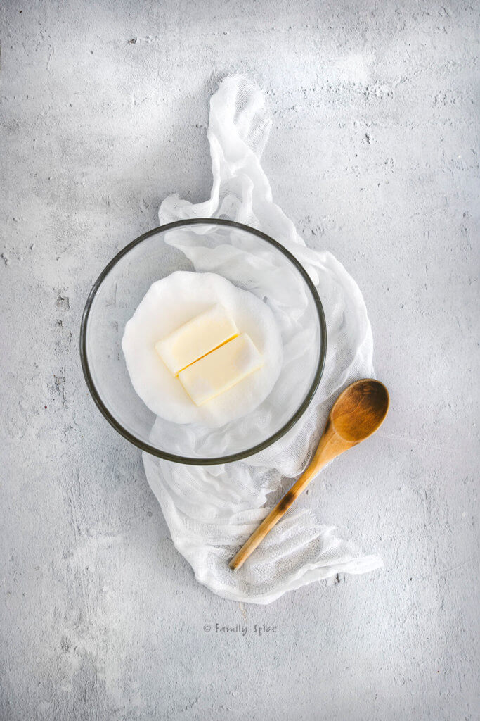 Butter and sugar in a glass mixing bowl with a wooden spoon next to it