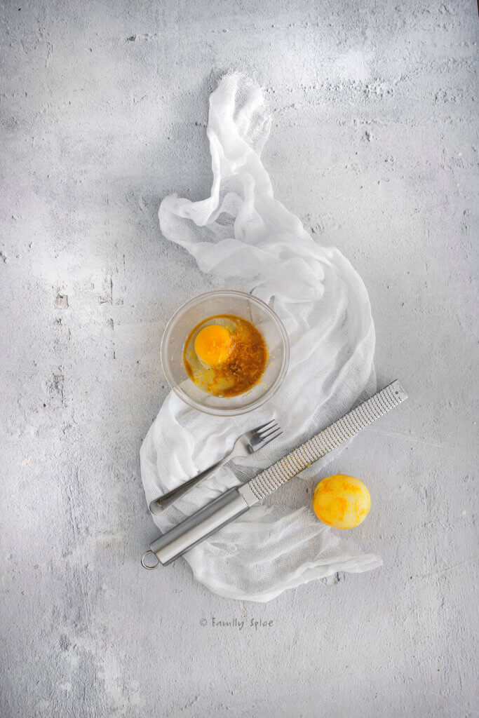 Egg, vanilla and lemon zest in a small glass bowl next to a lemon, microplane and fork