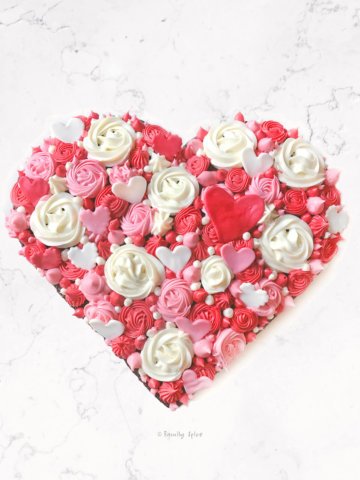 Chocolate heart cake decorated in various colored rosettes and studded with fondant hearts