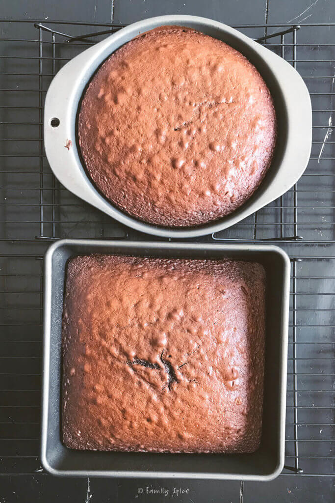 Freshly baked chocolate cake in a round pan and in a square pan on cooling racks