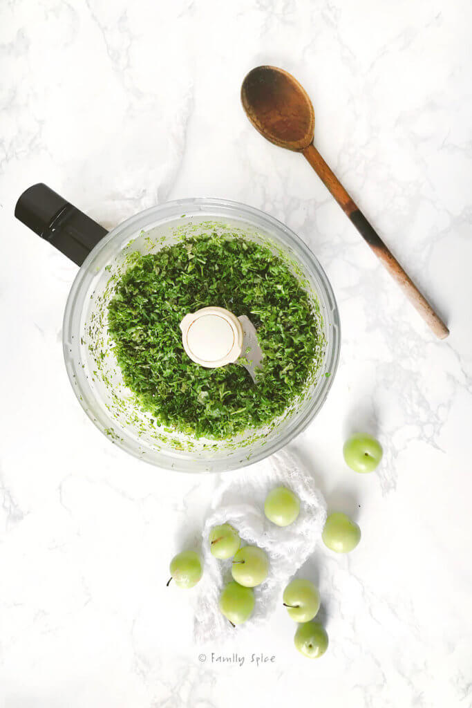 Fresh mint and parsley chopped in a food processor with green plums and a wooden spoon next to it