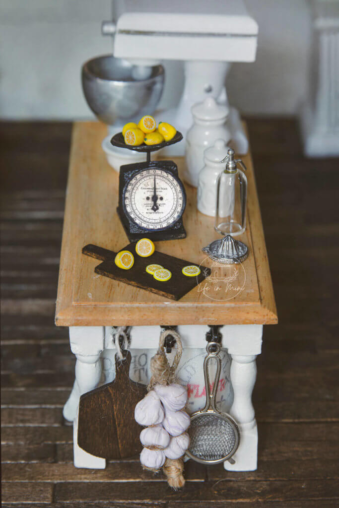 A dollhouse kitchen counter with miniature scale and lemons on a cutting board