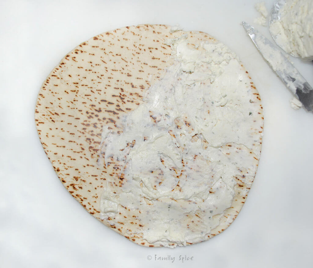 Top view of a pita round with flavored cheese spread over half of it