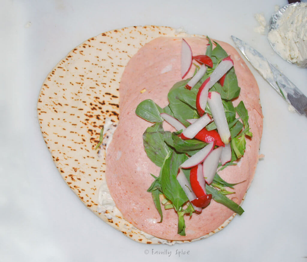 Top view of a pita round with mortadella, herbs and radishes on half of it