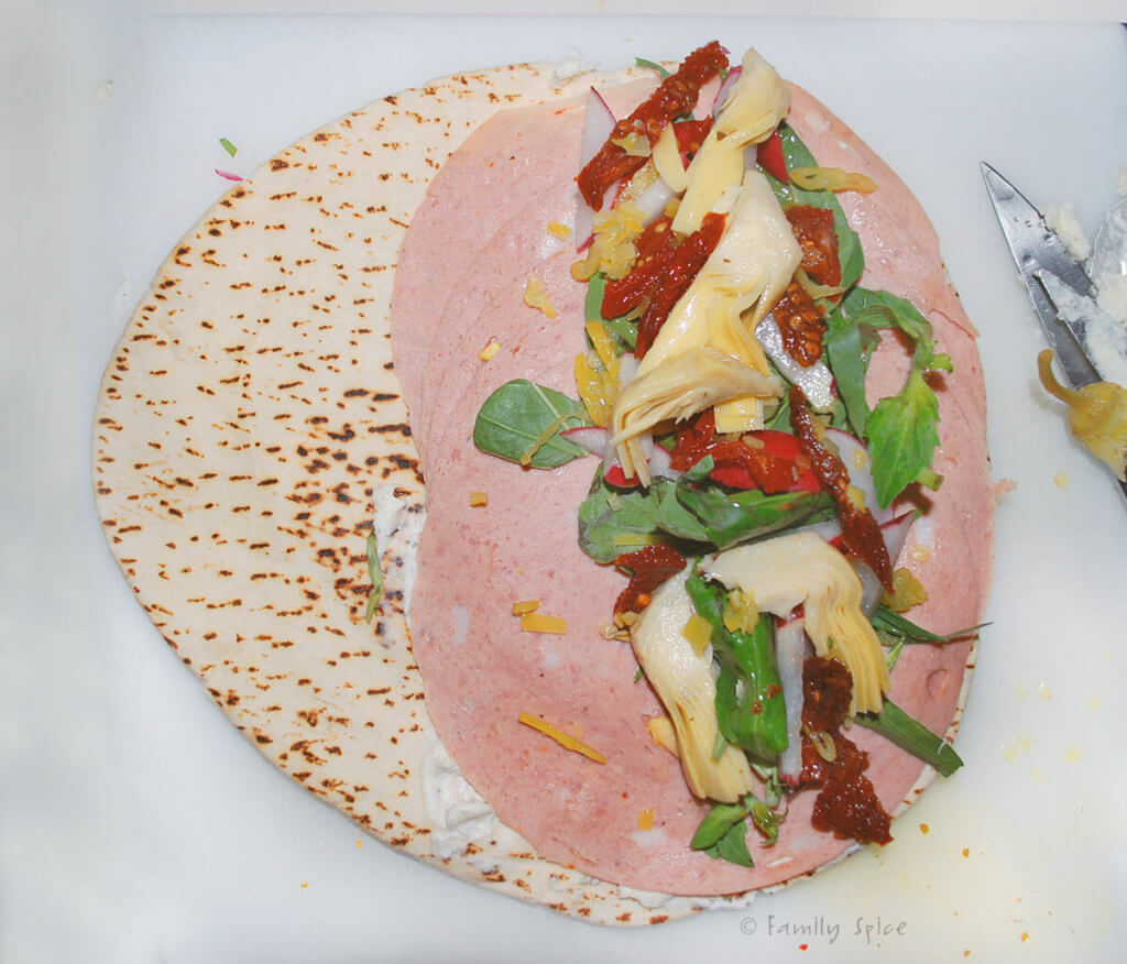 Top view of a pita round with mortadella, herbs, radishes, artichoke hearts and sun dried tomatoes on half of it