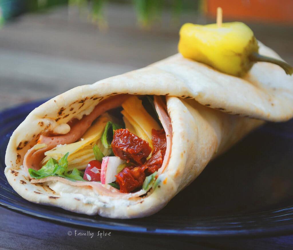 A Mediterranean wrap sandwich on a blue plate