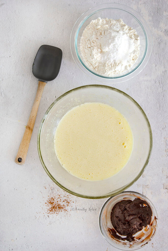 Cake batter in a mixing bowl with a bowl of flour and cocoa paste next to it